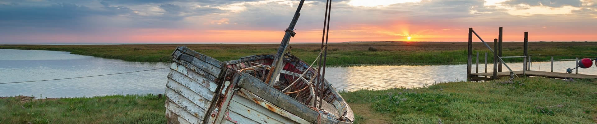 Sunrise over abandoned fishing boat at Thornham, Norfolk